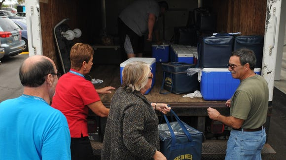 Meals on Wheels volunteers in Melbourne recently remove food packages from a truck before taking off on their delivery routes.