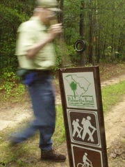 -  A hiker continues on the Palmetto Trail after walking along Greewood Road.