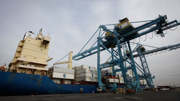 Shipping containers are loaded and unloaded from a waiting cargo ship at the Port of Wilmington.