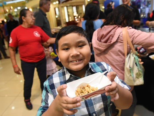 Jude Almazan, 7, shows his free school food, a serving of Northern Cheeseburger Pasta, during the Guam Department of Education 2018 Fourth Annual DOE Fair at Agana Shopping Center in Hagåtña, Aug. 4, 2018.