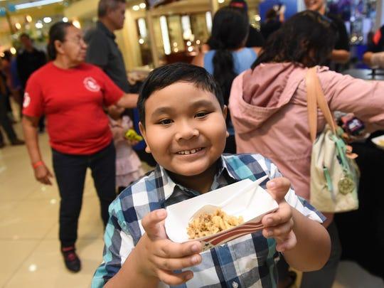 Jude Almazan, 7, shows his free school food, a serving