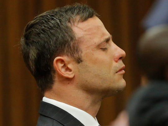 Oscar Pistorius reacts in the dock in Pretoria, South Africa, Thursday Sept. 11, 2014 as Judge Thokozile Masipa reads notes as she delivers her verdict in Pistorius' murder trial. The South African judge in Oscar Pistorius? murder trial said Thursday that prosecutors have not proved beyond a reasonable doubt that the double-amputee Olympic athlete is guilty of premeditated murder.