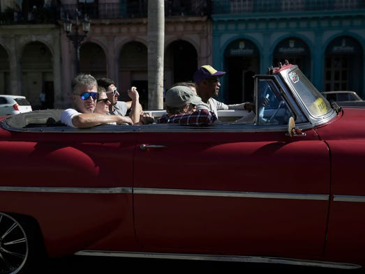 Tourists ride through the streets in a classic car