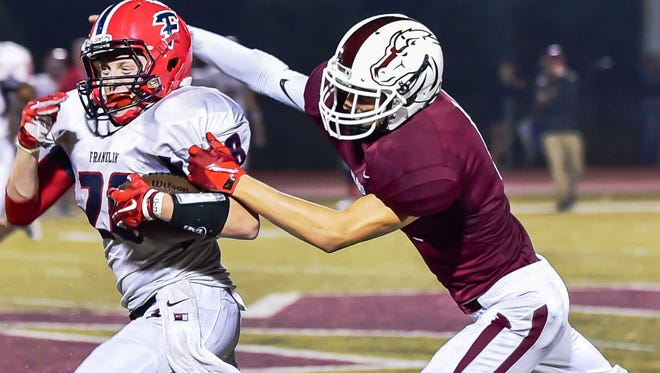 Milford's Isaac Phillips (right) tries to bring down Franklin ball carrier Nate Binkiewicz.