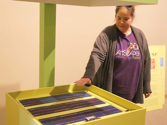 """Collections Manager Lizz Ricci demonstrates how a display featuring solar cells works as part of the """"Green Revolution"""" exhibition opening today at the Farmington Museum at Gateway Park."""