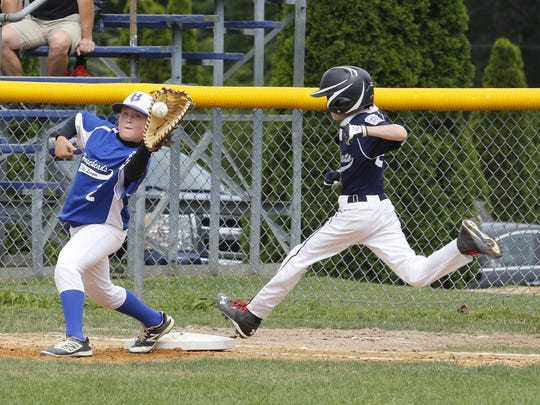 Horseheads first baseman Logan Moore catches the ball as Gunnar Tebo of Big Flats is called out at first base Saturday during Horseheads' 10-0 win in the District 6 Little League 9-11 championship game in Corning.