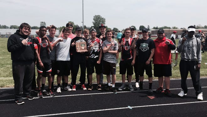 The Crestview boys, led by triple winner Cameron Shifflet (with plaque) and head coach Paul Gladden (second from right) celebrate Saturday's Division III district track championship.