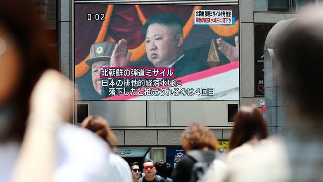 People walk near a screen showing a file image of North Korean leader Kim Jong Un with a report of North Korea's missile launch, in Osaka, western Japan on May 29, 2017.