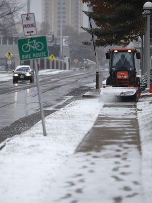 A tractor clears snow off sidewalks on the campus of Missouri State on Sunday, Nov. 16, 2014.