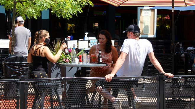 A couple is served on the outdoor patio at Wally's Bar & Grill in Saugatuck. The patio extends into the street to aid social distancing.