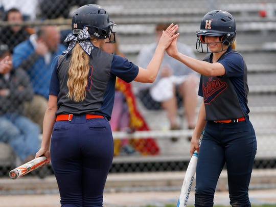 Dani Brewer, left, and Katie Switzer of Harrison exchange a high five after Brewer scored in the bottom of the sixth inning against Benton Central Thursday, May 11, 2017, in West Lafayette. The Raiders shut out the Bison 4-0.