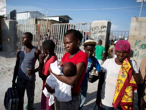Milene Monime, de 16 años, con su hijo de 2 meses de edad, Jefferson Thezan, se encuentra junto con otros inmigrantes haitianos recién deportados de República Dominicana, en el cruce fronterizo de Malpasse, Haití. (Foto: Rebecca Blackwell, AP