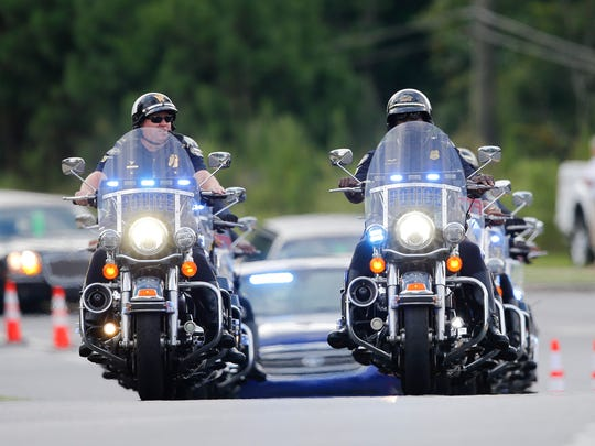 Police officers on motorcycles led a procession of mourners to a funeral for Bobbi Kristina Brown Saturday, Aug. 1, 2015, in Alpharetta, Ga.
