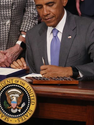 President Obama signs a chemical safety bill during an event in the Eisenhower Executive Office Building Wednesday. The bill amends the Toxic Substances Control Act to revise the process and requirements for evaluating and determining whether regulatory control of a chemical is warranted.