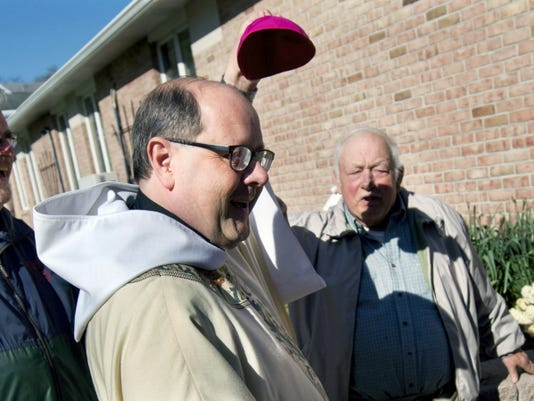 Long-time member Jerry Zurick, right, jokes with bishop-elect, Father Edward Malesic, that his bald head also needs a cap because of the bright sun, so Malesic jokes by motioning to give him the cap Sunday at Holy Infant Parish in York Haven. Bishop-elects are required to wear the head cover as bishops.  Malesic was appointed bishop of the diocese of Greensburg.