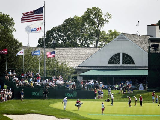Fans watch golfers practice putting on the 18th hole during a practice round for the U.S. Women's Open golf tournament at Lancaster Country Club on Tuesday.