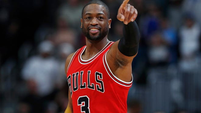 Chicago Bulls guard Dwyane Wade gestures to players from the Denver Nuggets as Wade takes the court in the first half of an NBA basketball game Tuesday, Nov. 22, 2016, in Denver.