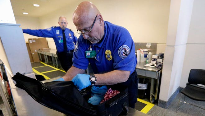 A TSA agent checks a bag at a checkpoint at Midway International Airport in Chicago. Spending for the Homeland Security Department hangs in the balance as Congress fights over unrelated immigration provisions attached by Republicans to the agency's annual spending bill.