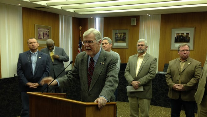 Rapides Parish Police Jury President Richard Billings (foreground) announces today that the Police Jury will proceed with its lawsuit against the city of Alexandria over property needed for parking as part of the Rapides Parish Coliseum renovation project.