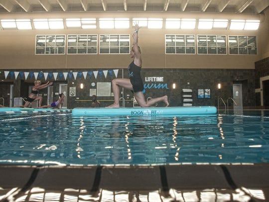 Leigh Ryan teaches a water yoga class at the LifeTime