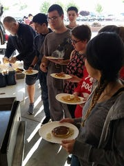 Students await syrup for their pancakes Monday morning during a pancake breakfast at Oñate High School.