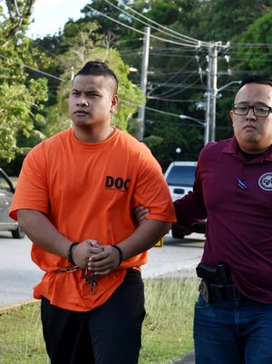 Criminal detectives escorts Marvin Rechim to the Guam Police Department's Hagåtña precinct on Feb. 8, 2018. Rechim is one of eight detainees arrested in connection with the Dec. 29 homicide of detainee Manson Isar.