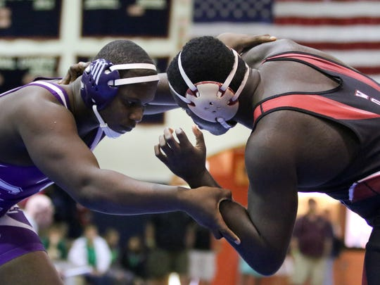 South Fort Myers H.S.'s Jordari Rene (red & black singlet) and Cypress Lake H.S.'s Jean Malivert (purple & white singlet) wrestle for third place in the 220 Weight Class during the LCAC wrestling tournament at Estero High School on Saturday, January 30, 2016.  Jordari Rene won. Photo by Gregg Pachkowski.