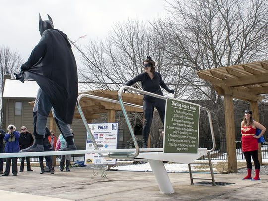 The stuff nightmares are made of: Mackensy Lunsford, aka Catwoman, whips Batman, aka John Boyle, at Saturday's Polar Bear Plunge fundraiser for Meals on Wheels.