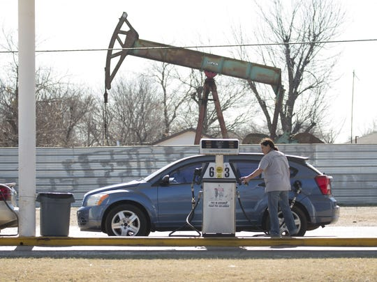 A motorist fills up at a gas station near an oil-field pumping rig in Oklahoma City.