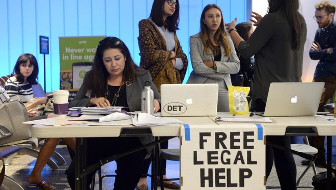 Immigration attorney Maggie Castillo, left, of the American Immigration Lawyers Association, offers her services to travelers affected by President Trump's travel ban at Los Angeles International Airport on June 29, 2017.