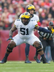 Michigan offensive lineman Cesar Ruiz blocks against