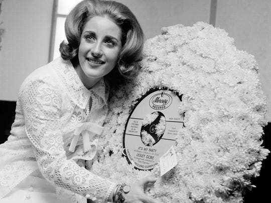 FILE - In this May 5, 1964, file photo, singer Lesley Gore hugs a flowered record at her 18th birthday party celebrated at the Delmonico Hotel in New York.