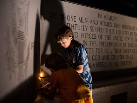 Cooper Larkan (right), 12, and his brother, Beck Larkan, 8, both of Stuart, light candles during a candlelight vigil at Memorial Park in downtown Stuart on Monday, Feb. 19, 2018, to honor the victims of the Feb. 14 mass shooting at Marjorie Stoneman Douglas High School in Parkland.