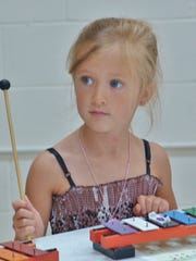 Levin Blair, 5, plays the xylophone during the Sing