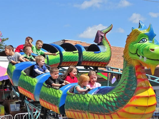 Young festival attendees enjoy their ride on the dragon wagon, a small coaster that was one of 17 rides and game booths  located on North Main Street during the festival.