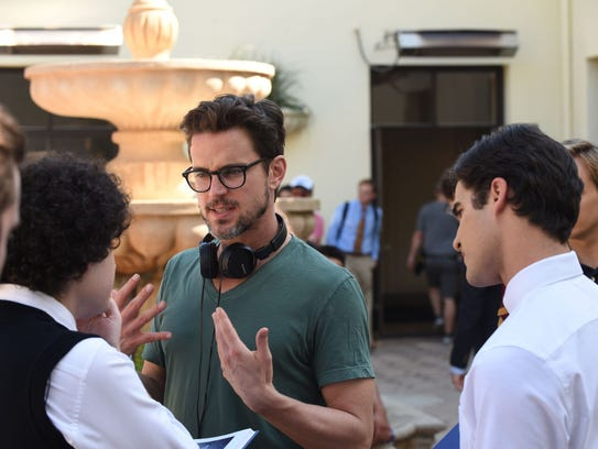 Director Matt Bomer, facing camera, talks to cast and