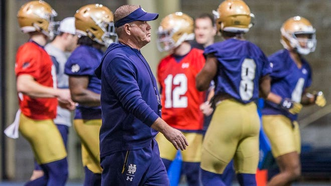 From March 2, 2019, Notre Dame coach Brian Kelly walks on the field during the NCAA college football team's spring practice in South Bend, Ind. The NCAA's football oversight committee expects to finalize a plan on Thursday to allow teams to conduct up to 12 unpadded, slow-speed practices, also know as walk-throughs, during the 14 days before the typical preseason begins in August. Kelly said the extra time on the field with a ball will be valuable for teaching schemes, but not necessarily for assessing player development.