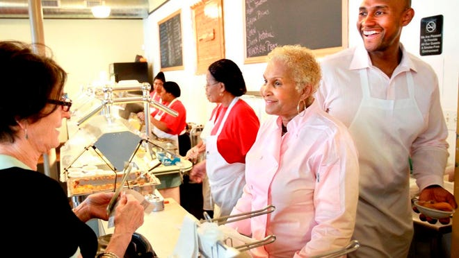 A customer picks up some to go food from Sweetie Pie's owner Robbie Montgomery, center, and Montgomery's son James Timothy Norman, right, at Sweetie Pie's in St. Louis on Tuesday, April 19, 2011. Norman, of Jackson, Miss., was arrested Tuesday, Aug. 18, 2020 in the March 14, 2016, fatal shooting of his nephew Andre Montgomery, who was gunned down near a park in St. Louis.
