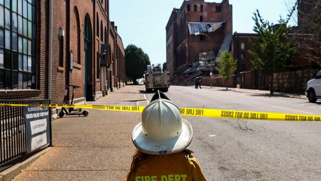 John Mcateer, 7, watches the firefighters inspect the scene where Building 20 of the Lemp Brewery Complex collapsed on Cherokee Street in South St. Louis on Sunday, August 23, 2020. The family lives a little way away from the scene and had to come out so he could check out the firefighters. The building housed a storage space for St. Louis Bicycle Works, who were currently storing around 700 bikes there. No one was in the building at the time of the collapse.