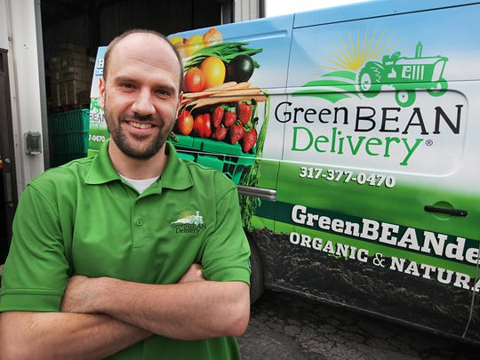 CEO of Green BEAN Delivery, Matt Ewer standing next to one of his delivery trucks.