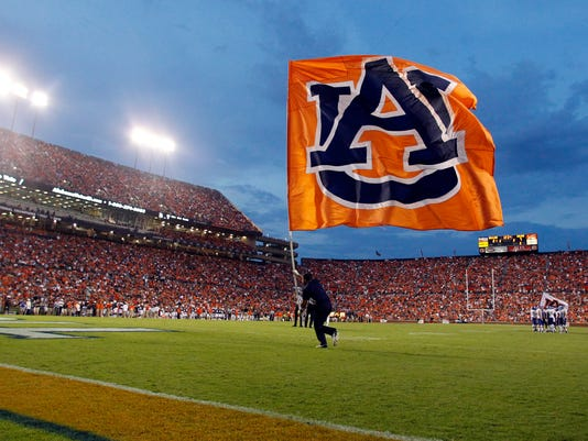 In this Sept. 6, 2014 photo, an Auburn cheerleader runs across the field with a flag after a touchdown during the first half of an NCAA college football game against San Jose State in Auburn, Ala. Ahead of the 2014 college football season, the AP asked its panel of Top 25 voters, who are known for ranking the nation's top teams each week, to weigh in on which stadium had the best game day atmosphere. Auburn's Jordan-Hare received recognition from the panel. (AP Photo/Butch Dill, File)