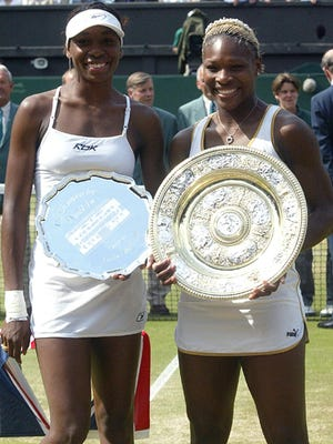 Serena Williams, right, and Venus Williams hold their trophies after the Women's Singles final on the Centre Court at Wimbledon on July 6, 2002. Serena won the match 7-6 (7-4), 6-3 to win the championship.