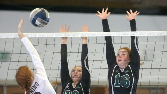 Ossining's Zoe Farmakopoulos has her shot defended by Yorktown's Macey Drezek (10) and Ryan Geary (16) during the annual Breast Cancer Awareness Volleyball Tournament at Hendrick Hudson High School in Montrose Sept. 9, 2017. Yorktown defeated Ossining in both games of their match.