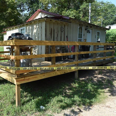 Crime scene tape surrounds the home that was shared