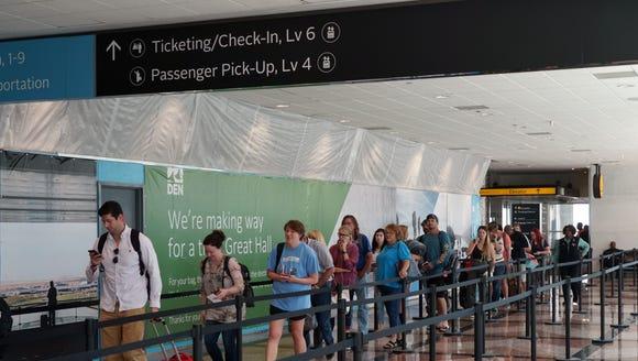 Passengers wait in a security line at Denver International