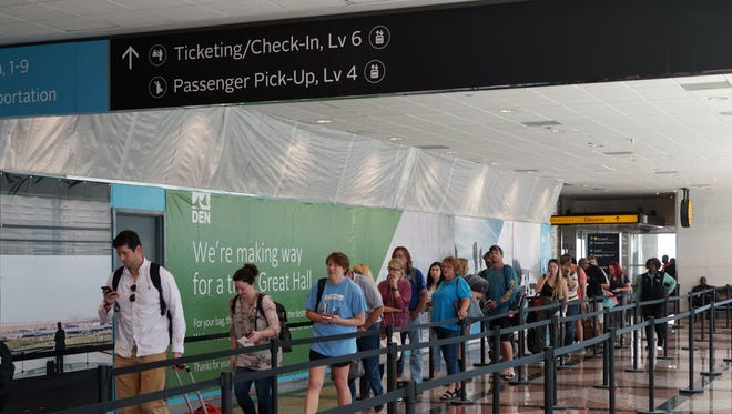 Passengers wait in a security line at Denver International Airport on July 16, 2018, near a sign alerting travelers to planned terminal renovations.