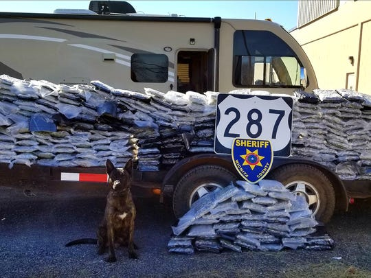A Wichita County Sheriff's Office K-9 deputy poses with about 480 pounds of marijuana and over 12 pounds of tetrahyrdocannabinol after a reported drug bust on U.S. Highway 287 on Friday.