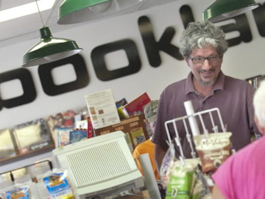 Andy Chock, owner of Bookland, helps out a customer in this August 2011 file photo. Bookland closed its doors July 14, 2013.