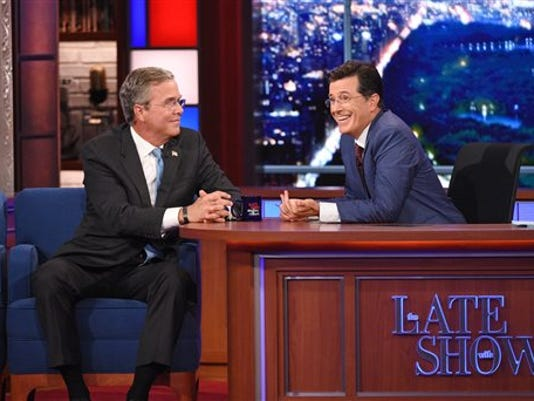 "Stephen Colbert, right, talks with Republican presidential candidate Jeb Bush during the premiere episode of ""The Late Show,"" Tuesday Sept. 8, 2015, in New York. Bush and actor George Clooney were the guests for Colbert's debut."