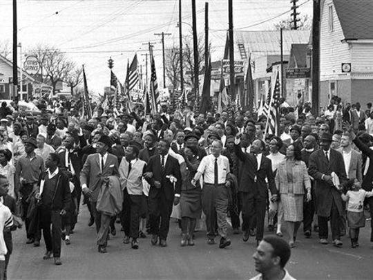 FILE - In this March 21, 1965 file photo, Dr. Martin Luther King, foreground row, fifth from right, waves as marchers stream across the Alabama River on the first of a five day, 50-mile march to the state capitol at Montgomery, Ala. (AP Photo/File)